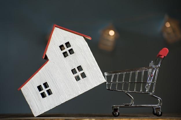Casa e carrinho de compras. comprando um conceito de hipoteca da casa.