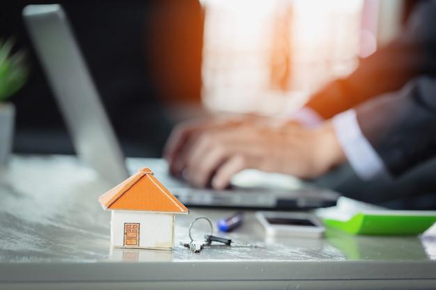 Casa e chave na mesa no escritório do agente imobiliário. conceito de compra de casa nova