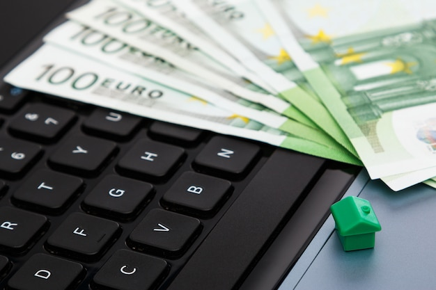 Casa e dinheiro sobre o teclado do laptop