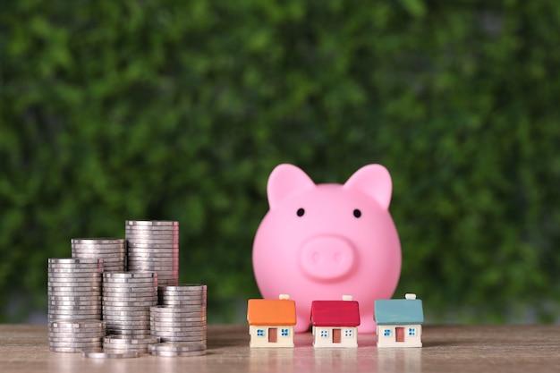 Casa e empilhamento de moedas, economizando o crescimento com o cofrinho na mesa de madeira e verde.