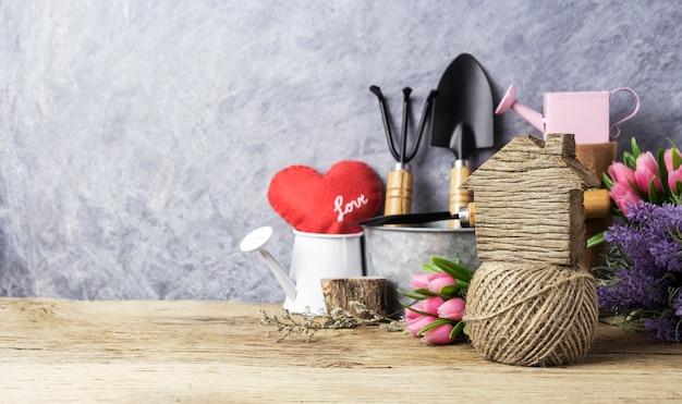 Casa e jardim conceito de ferramentas de jardinagem e flores na madeira velha