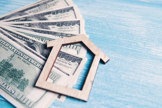 Casa e notas de dólar na mesa