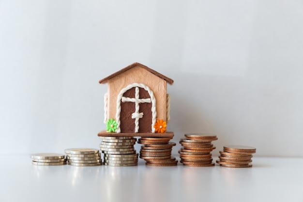 Casa em miniatura com moedas de pilha em fundo branco