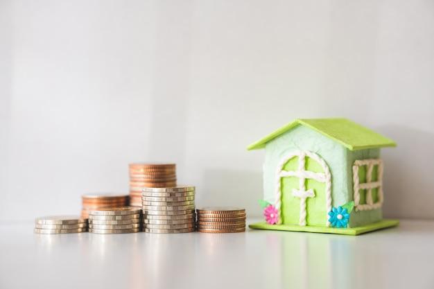 Casa em miniatura com moedas de pilha no fundo branco, usando como propriedade e conceito financeiro