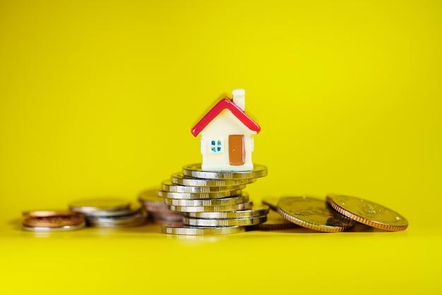 Casa em miniatura de uma pilha de moedas usando como propriedade imobiliária e conceito financeiro