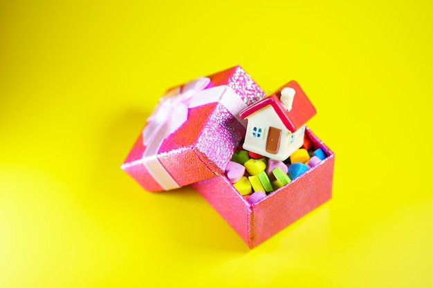 Casa em miniatura em caixa de presente em fundo amarelo usando como propriedade imobiliária e conceito de família