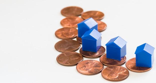 Casa em miniatura em pilhas de moeda de 1 centavo, imobiliário e conceito de finanças