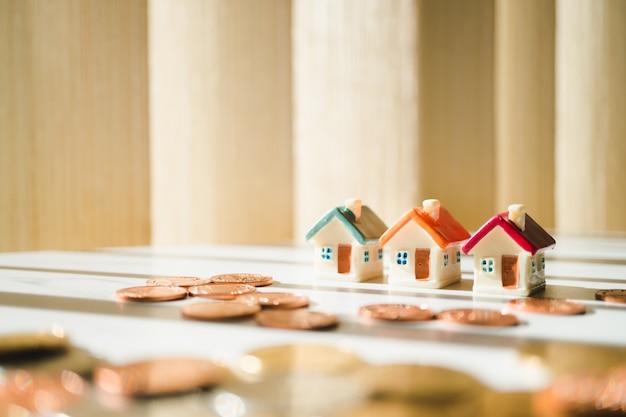 Casa em miniatura na pilha moedas usando como propriedade e conceito financeiro