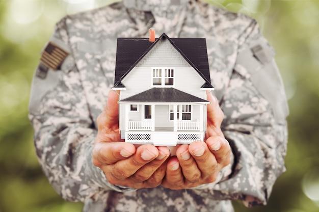Casa em miniatura nas mãos do soldado, close-up