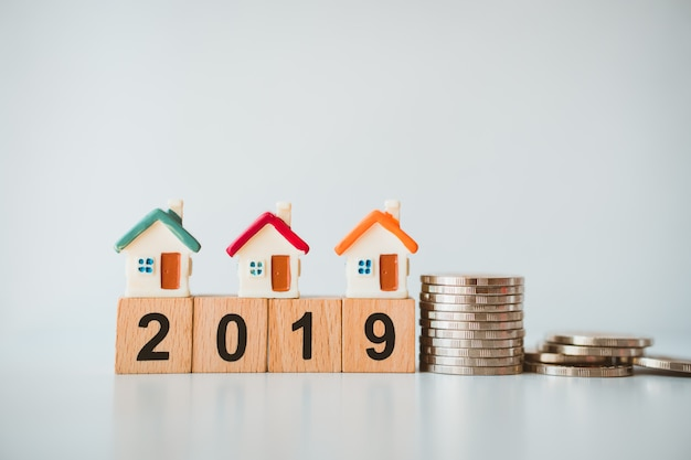 Casa em miniatura no ano de madeira 2019 bloco com moedas de pilha usando como negócios e conceito de propriedade