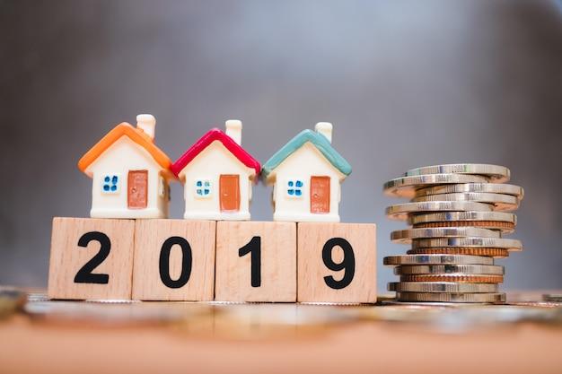 Casa em miniatura no ano de madeira do bloco 2019 com pilha de moedas usando como negócios e conceito de propriedade