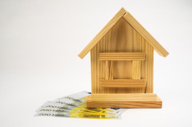 Casa em miniatura sobre dinheiro isolado no fundo branco.