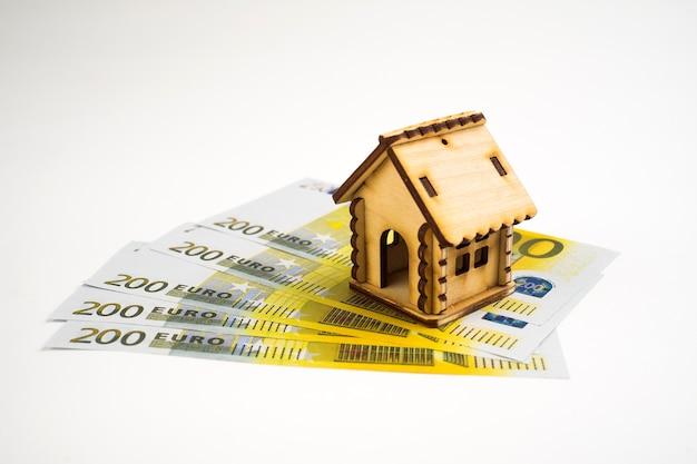 Casa em miniatura sobre o dinheiro isolado no fundo branco.