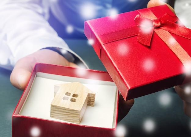 Casa em uma caixa de presente nas mãos de um empresário e neve. imóveis na temporada de inverno.