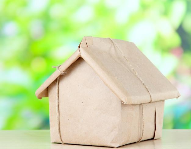 Casa embrulhada em papel kraft marrom sobre vegetação desfocada