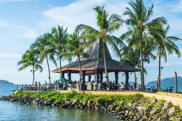 Casa entre palmeiras e mar