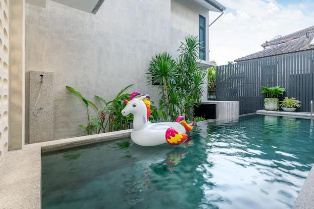 Casa exterior com piscina e unicórnio flutuante na casa