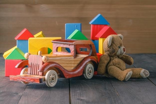 Casa feita de blocos de madeira para montar, perto de atoy e um carro de brinquedo de madeira