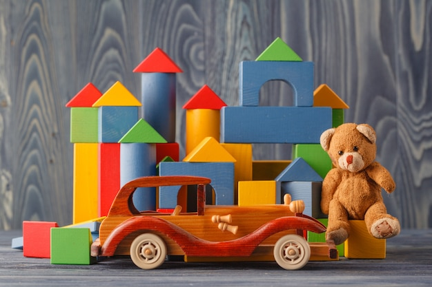 Casa feita de blocos de madeira para montar, perto de um brinquedo e um carro de brinquedo de madeira