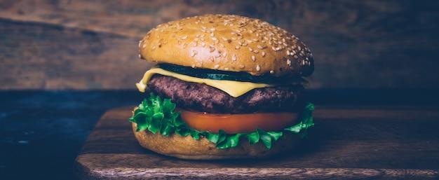 Casa feita de hambúrguer (cheeseburger) com carne em um fundo de madeira. casa clássica feita burger.