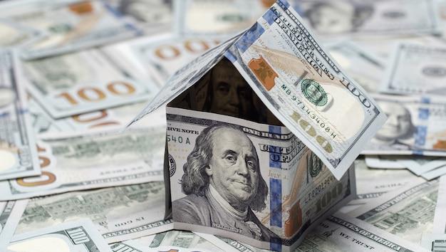 Casa feita de notas de 100 dólares em fundo de dinheiro americano