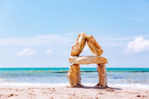 Casa feita de pedras contra o mar. pedras do mar no mar