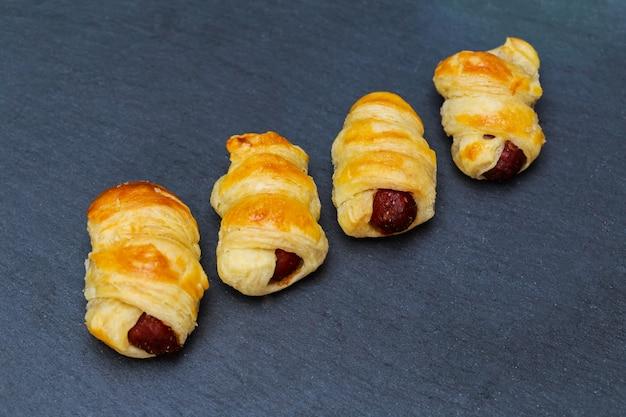 Casa feita de porcos em um cobertor. salsichas enroladas em massa de croissant