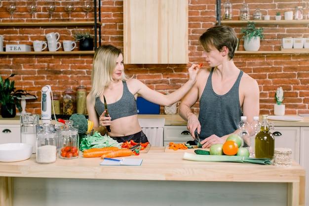 Casa. felizes juntos. marido e esposa. preparando comida. cozinha. apartamento. natural. legumes. amem-se uns aos outros. maternidade. relaxamento. felicidade. paternidade. vida domestica.