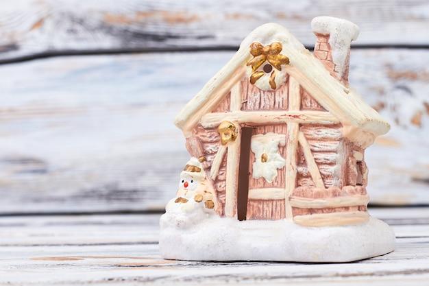Casa gingerbred na neve em fundo de madeira.