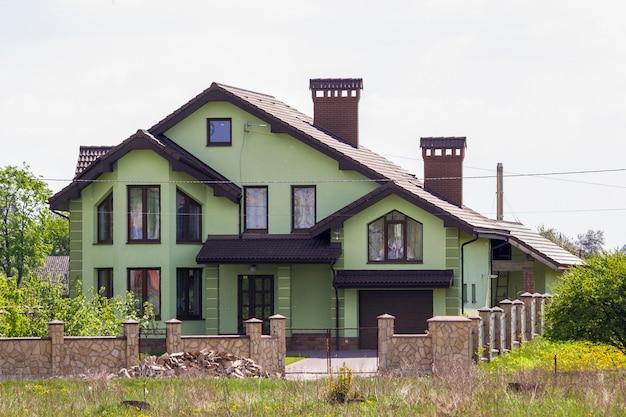 Casa grande e bonita de tijolos verdes luxuosos com garagem, garagem pavimentada, duas chaminés, telhado de azulejos e cerca de pedra entre árvores verdes na vizinhança tranquila. arquitetura moderna e conceito imobiliário.