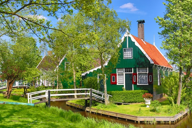 Casa holandesa verde tradicional com pouca ponte de madeira contra o céu azul na vila de zaanse schans, países baixos