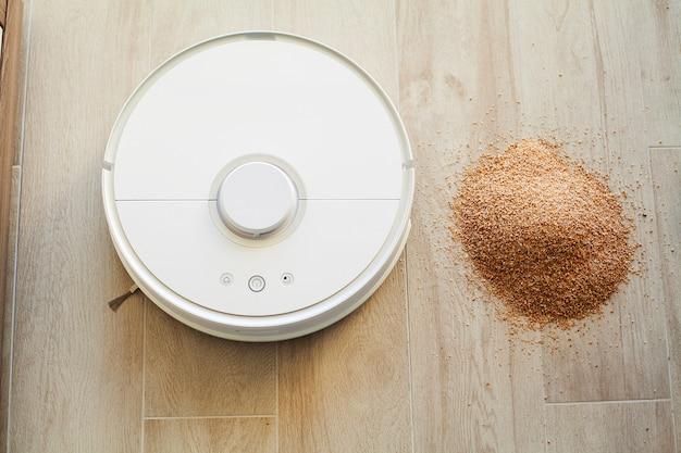Casa inteligente, aspirador de pó robô executa a limpeza automática do apartamento em um determinado momento