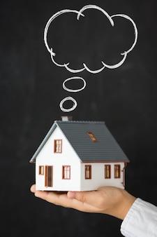 Casa inteligente casa na mão contra o fundo do quadro-negro conceito imobiliário espaço de cópia