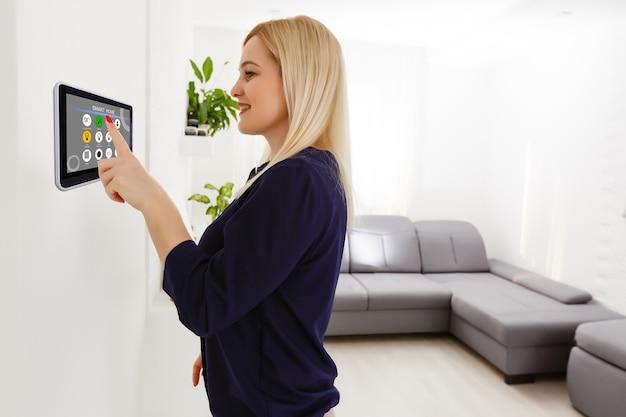 Casa inteligente. mulher bonita e alegre olhando para o painel sensorial enquanto o pressiona