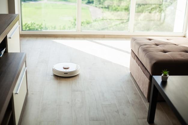 Casa inteligente. o robô do aspirador de pó funciona no assoalho de madeira em uma sala de visitas.