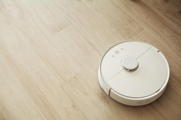 Casa inteligente, robô aspirador funciona em assoalho de madeira em uma sala de estar,