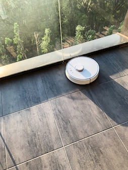 Casa inteligente. robô de aspirador de pó é executado no chão em uma sala de estar.