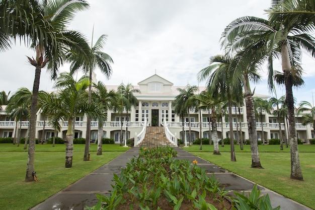 Casa luxuosa nas maurícias, com um gramado verde e palmeiras.