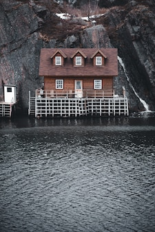 Casa marrom e branca ao lado do corpo de água