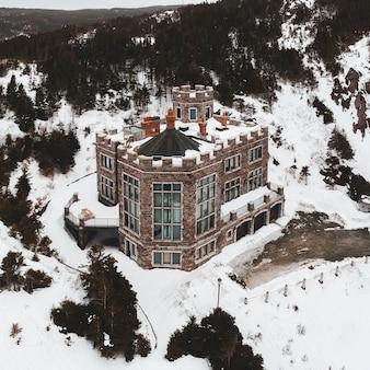 Casa marrom e branca em terreno coberto de neve