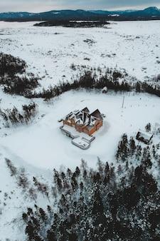 Casa marrom e preta no campo de neve ao lado de árvores durante o dia