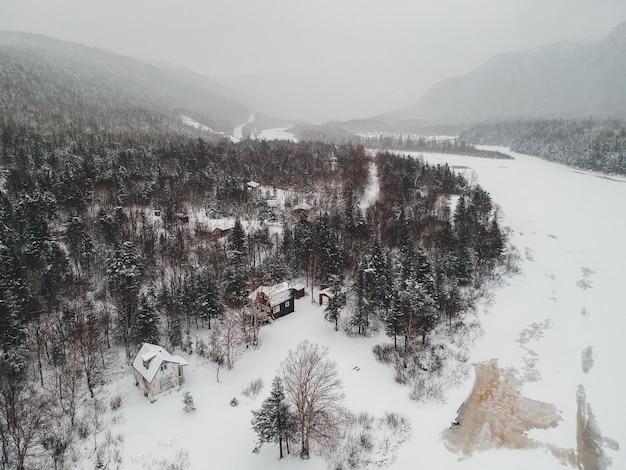 Casa marrom no chão nevado, rodeado por árvores