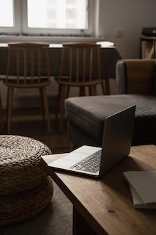 Casa mínima estética, design de interiores de sala de estar. mesa de madeira com laptop, pufe de rattan, bancos