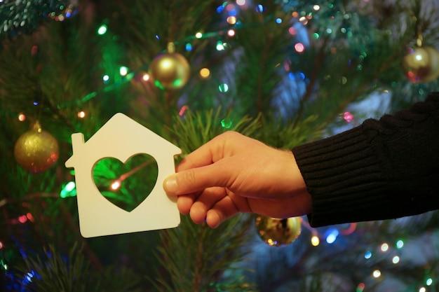 Casa minúscula com o coração na mão do homem em fundo de natal