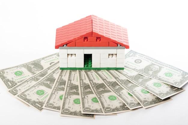 Casa modelo de brinquedo acima do dinheiro