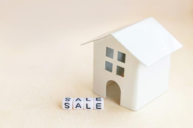Casa modelo de brinquedo em miniatura com a inscrição venda letras wor