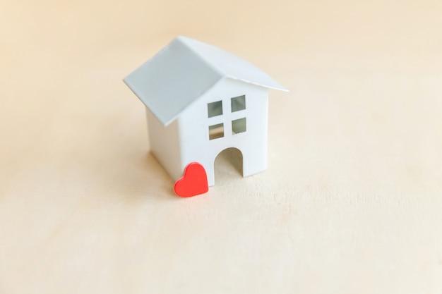 Casa modelo de brinquedo em miniatura com coração vermelho em pano de fundo de madeira. eco village abstrato base ambiental. conceito de ecologia de casa de sonho doce seguro de propriedade de hipoteca imobiliária