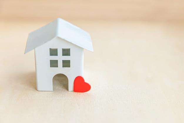 Casa modelo de brinquedo em miniatura com coração vermelho em pano de fundo de madeira