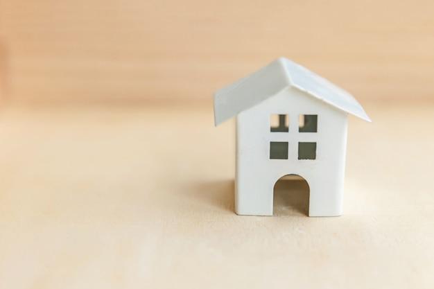 Casa modelo de brinquedo em miniatura no pano de fundo de madeira. eco village abstrato base ambiental. conceito de ecologia de lar doce hipoteca de seguro de propriedade imobiliária