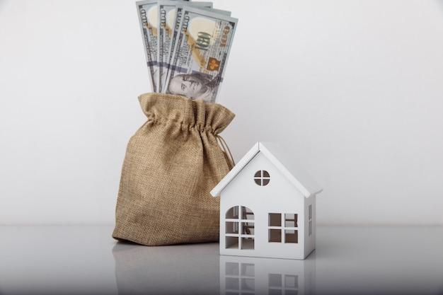 Casa modelo e bolsa de dinheiro com notas de dólar